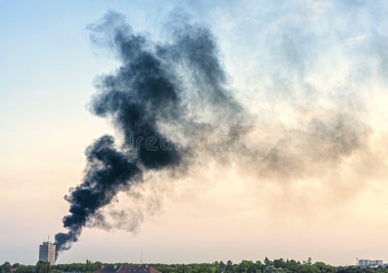 Plume de fumée d'un feu au-dessus de ville au coucher du soleil photographie stock libre de droits