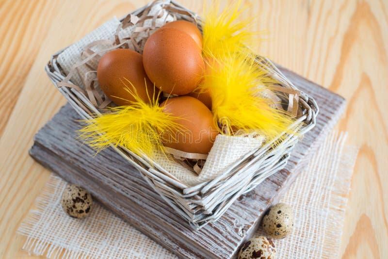 Plume de Pâques flatlay plume jaune avec des oeufs de pâques sur le fond en bois photo libre de droits
