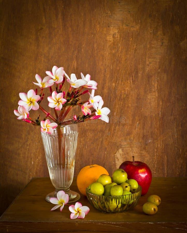 Plumeriabloem en veel fruit op oude houten lijst stock fotografie