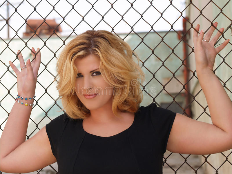 Download Plump Blond Woman Against Chain Linked Fence Stock Image - Image: 13546923