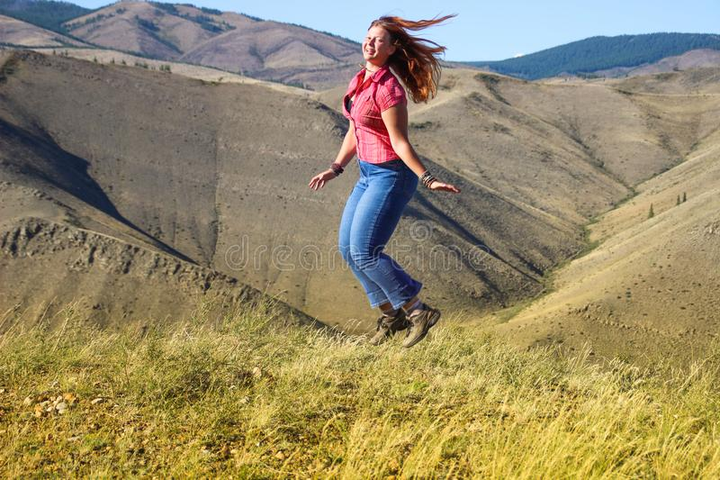 Plump white haired caucasian girl in jeans and hiking boots jumping on the field royalty free stock image