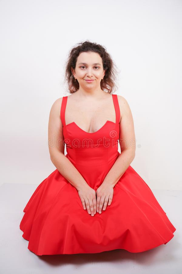 Plump woman in a red pinup dress. chubby fashionable girl standing on white background in Studio royalty free stock photo