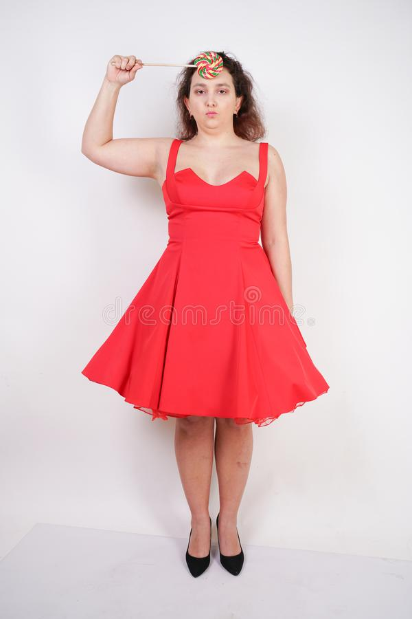 Plump woman in a red pinup dress. chubby fashionable girl standing on white background in Studio stock photos