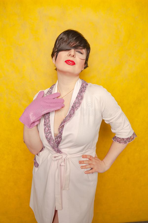Plump woman with short black hair stands in a pink Bathrobe with a rubber potholder glove on a yellow Studio background. Alone royalty free stock photo