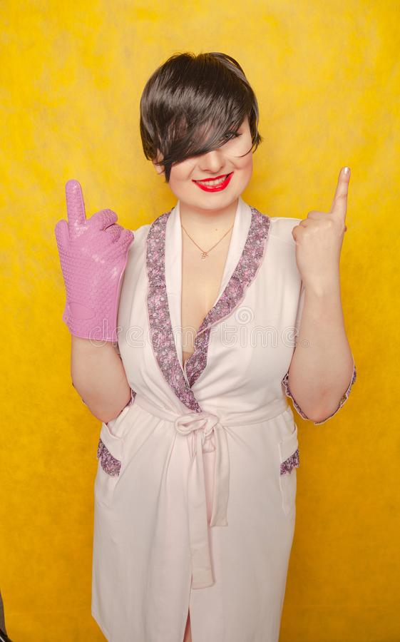 Plump woman with short black hair stands in a pink Bathrobe with a rubber potholder glove on a yellow Studio background. Alone royalty free stock photography