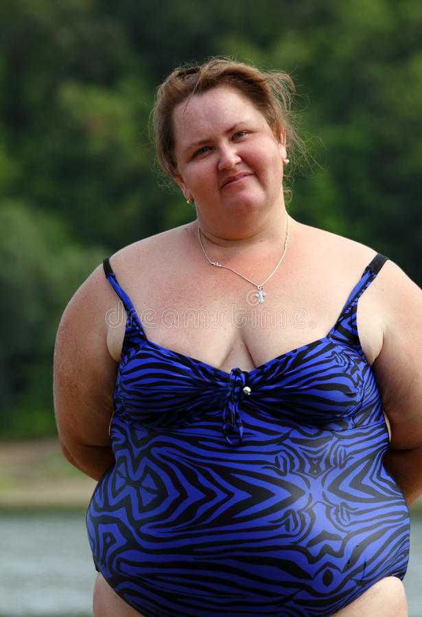 Plump woman standing near river stock photography