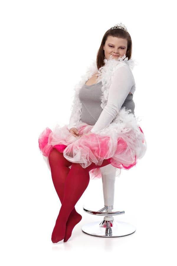 Plump woman in tiara and pink tutu. Plump woman posing in tiara and pink tutu, sitting on chair stock photography