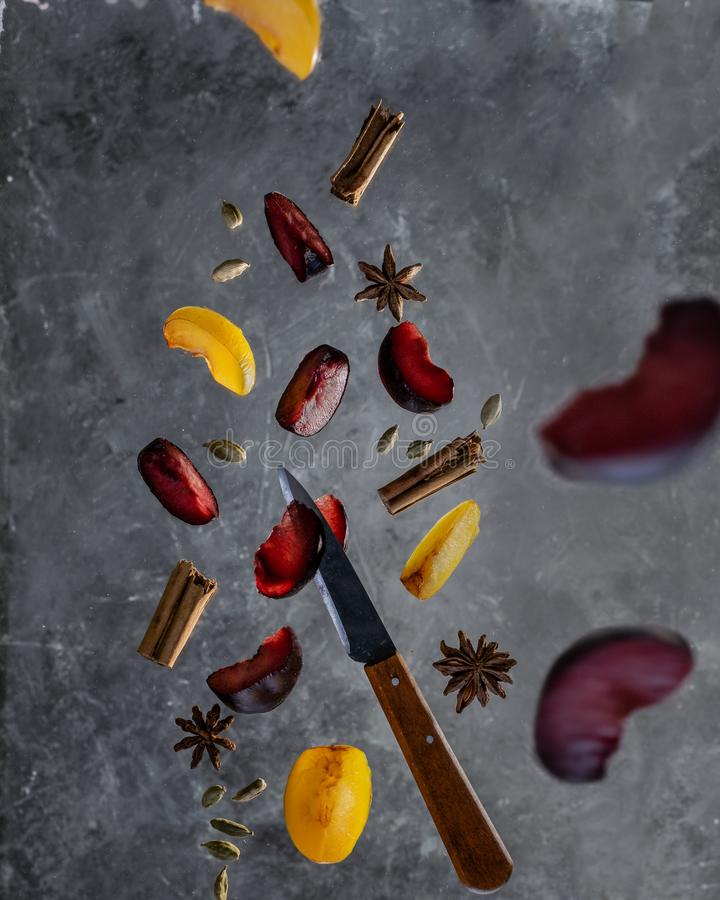 Plums with cinnamon, cardamom and anise spices in flying motion royalty free stock photography