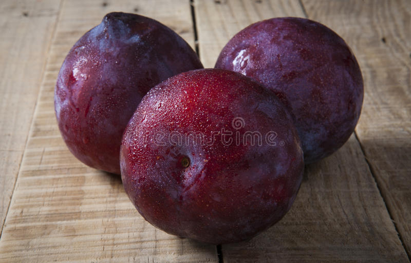 Plums over rustic wooden table royalty free stock photos