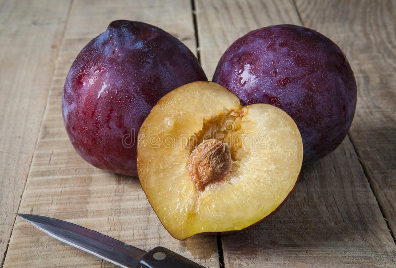 Plums over rustic wooden table stock images