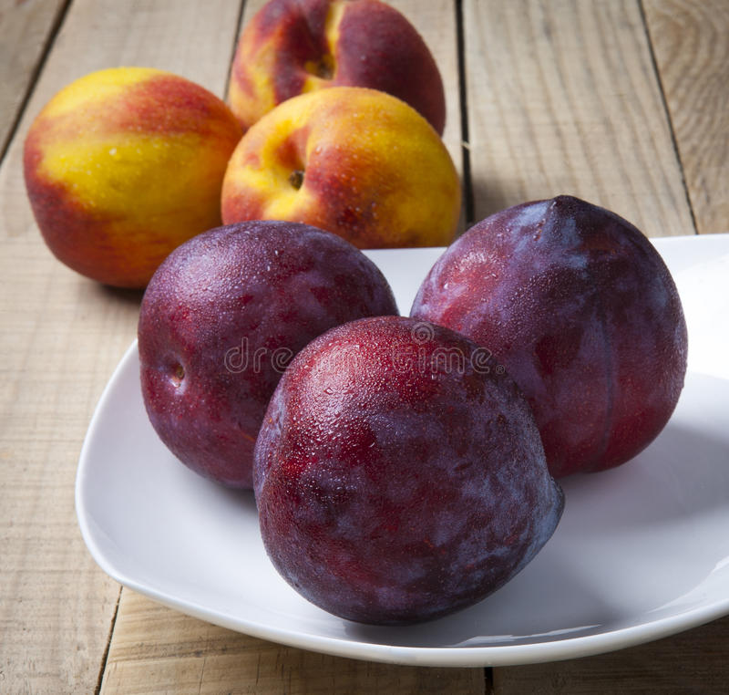 Plums and peaches over rustic wooden table stock images