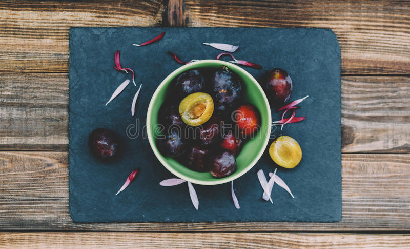 Plums In Plate. Plums in green plate on home kitchen table royalty free stock image