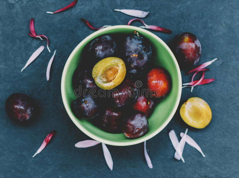 Plums In Plate. Plums in green plate on home kitchen table stock photo