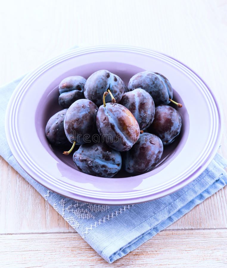 Plums in a purple bowl royalty free stock photos