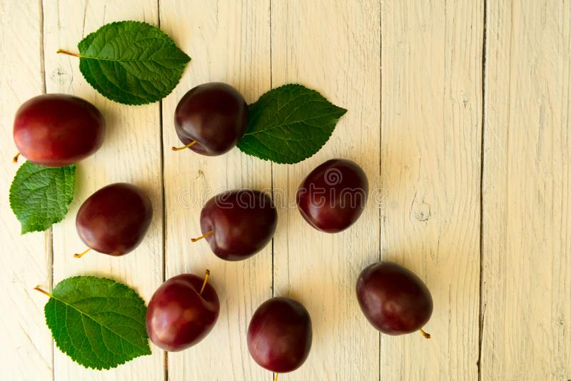 Plums on a white wooden background. Many beautiful plums with leaves. Top view. Copy space. royalty free stock photos