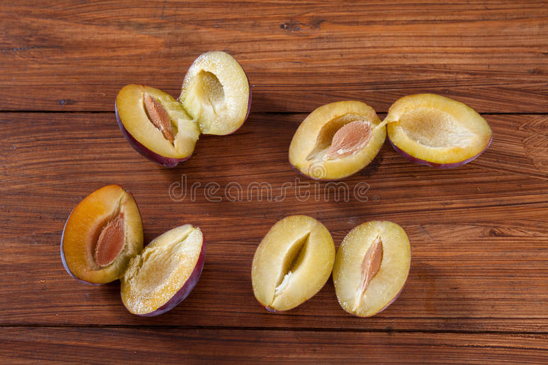 Plums on wood, halfed. On wooden background royalty free stock photos