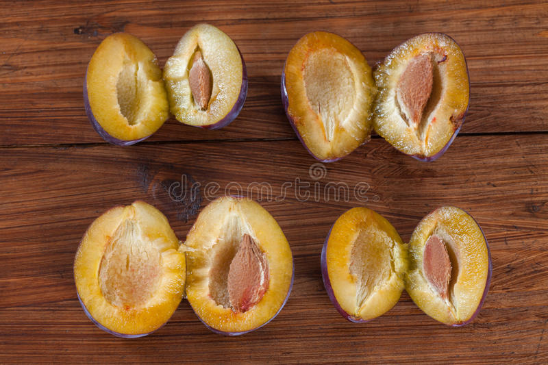 Plums on wood, halfed. On wooden background royalty free stock photo