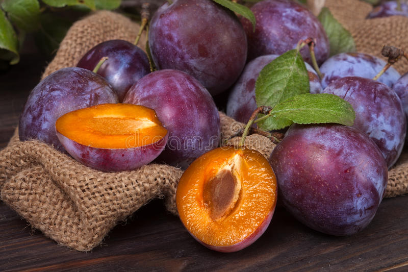 Plums on the wooden background with sackcloth.  stock image