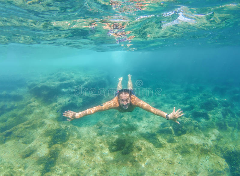 Plunge into the deep blue sea. Underwater photo of a man swimming in the sea