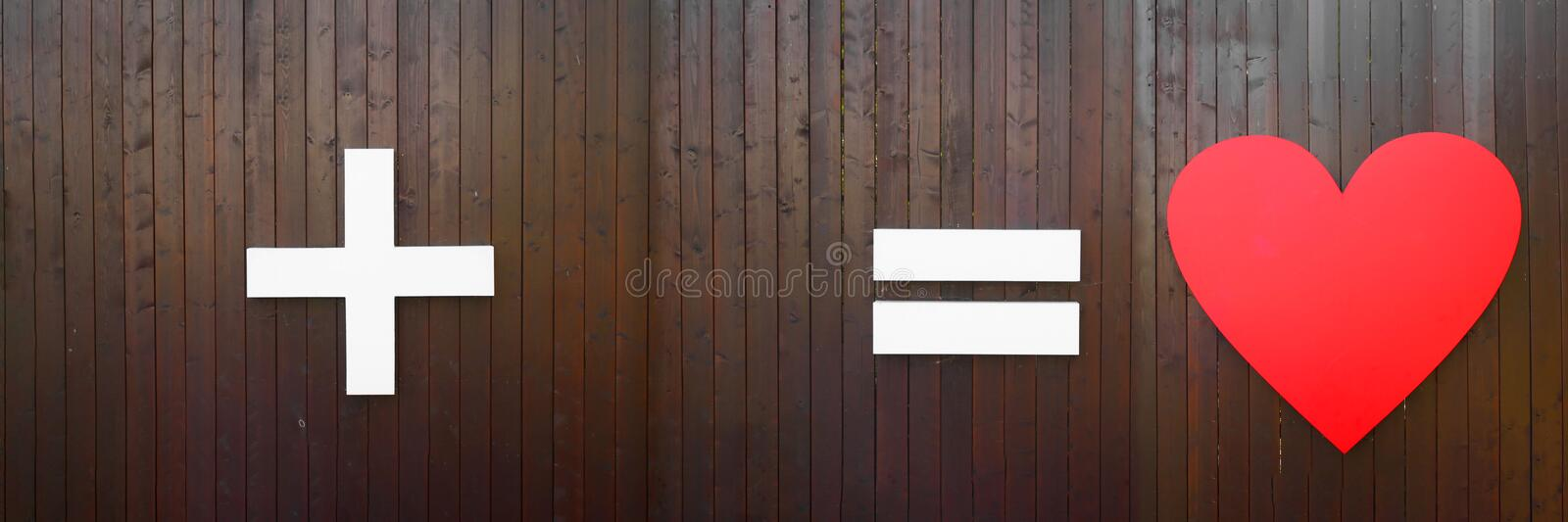 Plus, equal and heart symbol on brown wooden wall. Long horizontal banner with copy space. Creative concept or wedding. Plus, equal and heart symbol on brown stock photos