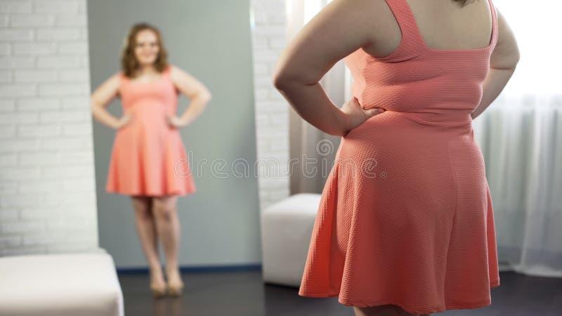 Plus-format flicka som beundrar sig i spegeln som tillfredsställs med utseende, övervikt arkivfoton