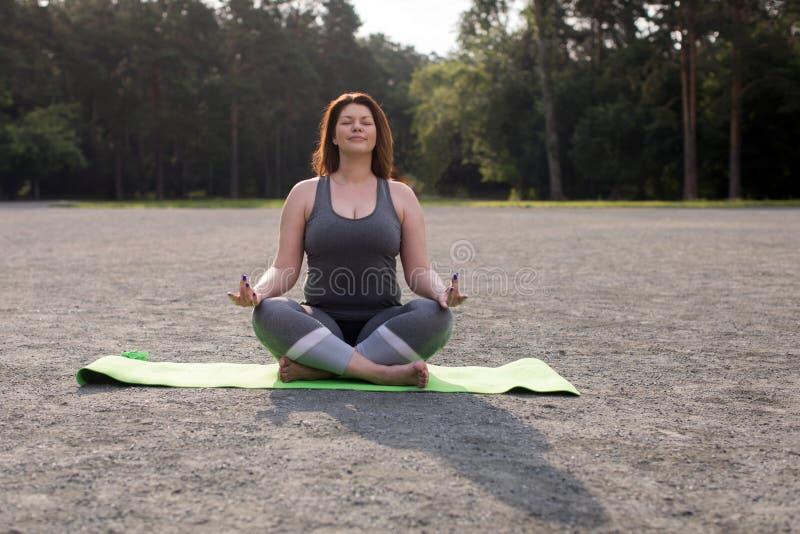 Plus formatflickan som utomhus mediterar yoga royaltyfri bild