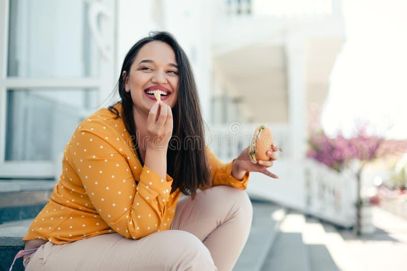 Plus formatkvinnan som går ner staden och äter hamburgaren royaltyfri foto