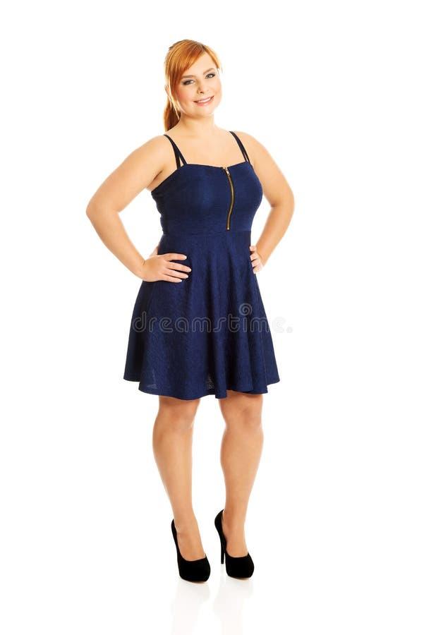 Plus formatkvinnan som poserar i kjol royaltyfri foto