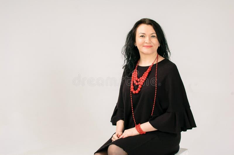 Plus formatmodell i svart klänning och rött etniskt halsbandsammanträde på stolen i studio kopieringsutrymme på vänstra sidan av royaltyfria bilder