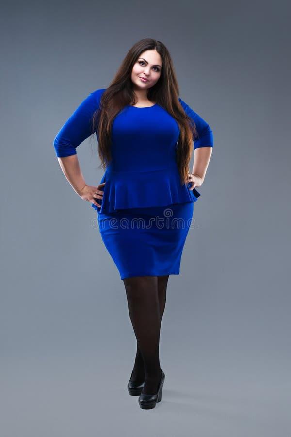 Plus formatmodemodell i blå klänning fet kvinna på grå studiobakgrund, överviktig kvinnlig kropp arkivfoto