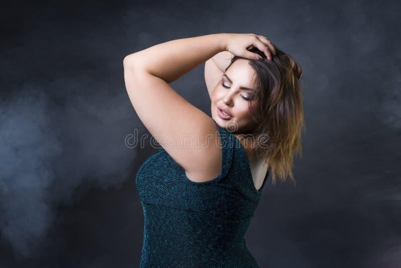 Plus formatmodemodell i grön aftonklänning fet kvinna på svart bakgrund, stående med yrkesmässig makeup royaltyfria bilder