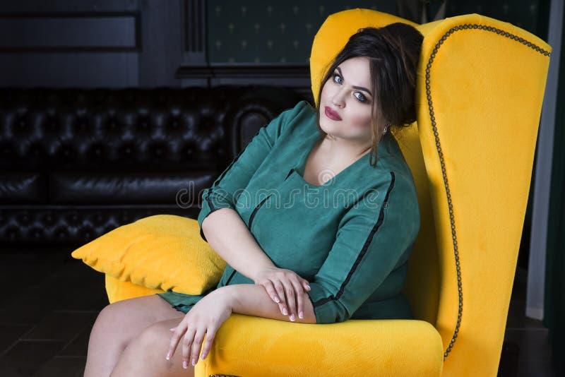 Plus formatmodemodell i grönt sammanträde för aftonklänning i gul fåtölj fet kvinna på lyxig inre arkivbilder