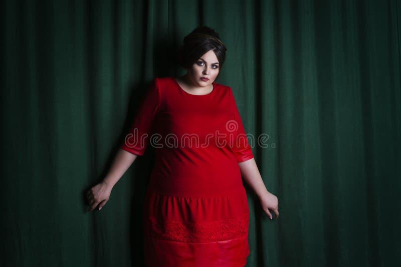 Plus formatmodemodell i röd aftonklänning fet kvinna på grön bakgrund royaltyfri foto