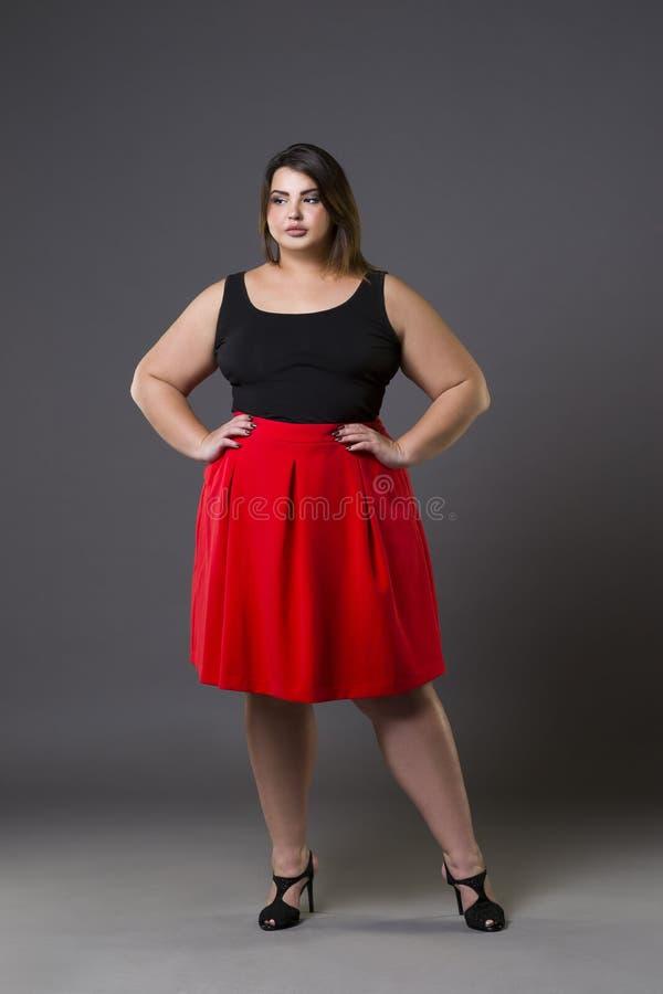 Plus formatmodemodell i röd kjol fet kvinna på grå bakgrund, överviktig kvinnlig kropp fotografering för bildbyråer