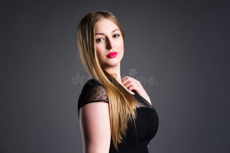 Plus formatmodemodell sexig fet kvinna på grå studiobakgrund, överviktig kvinnlig kropp arkivfoto