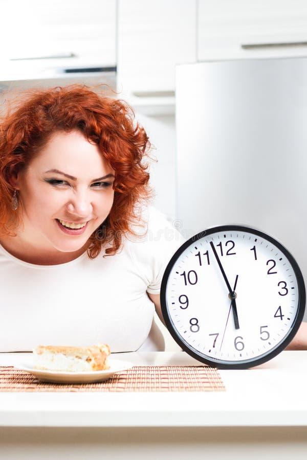 Plus grootte gulzige eet het meisje zoete pastei Het hongerige vette model zit door Th royalty-vrije stock afbeelding