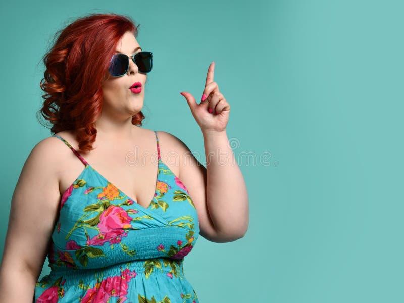 Plus-grootte te zware dame in zonnebril en sundress punt haar vinger als heeft zij omhoog een idee bij de ruimte van het vrije te royalty-vrije stock foto's