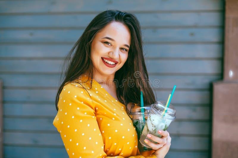 Plus grootte vrouw haalt het drinken cocktail over de muur van de stadskoffie weg royalty-vrije stock fotografie