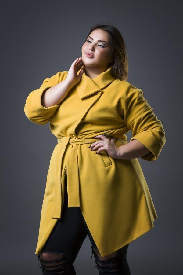 Plus groottemannequin in gele laag en zwarte hoed, vette vrouw op grijze achtergrond, te zwaar vrouwelijk lichaam stock fotografie