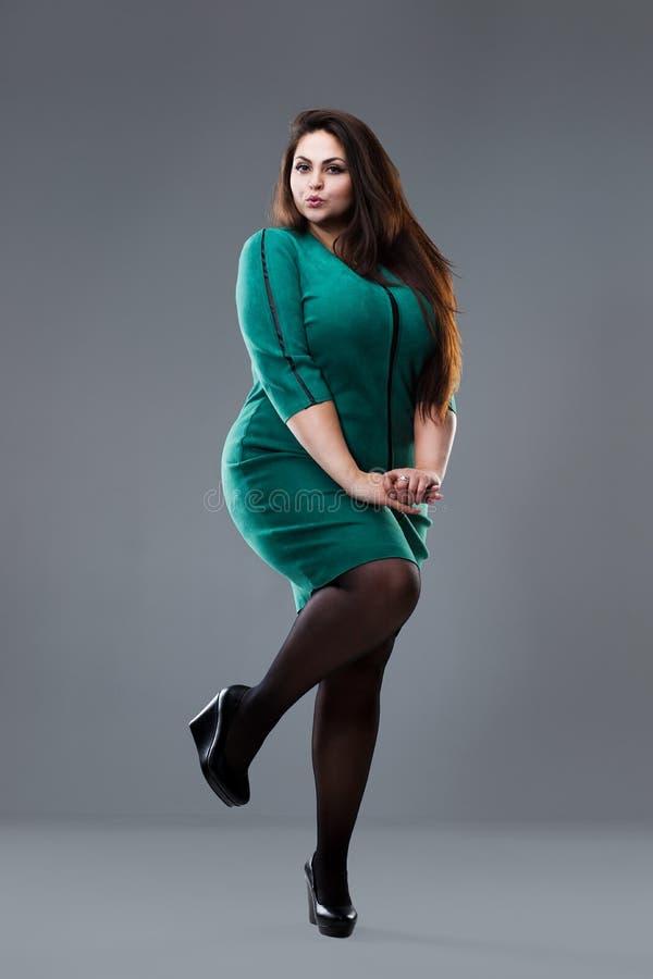 Plus groottemannequin in groene kleding, vette vrouw op grijze studioachtergrond, te zwaar vrouwelijk lichaam stock foto's