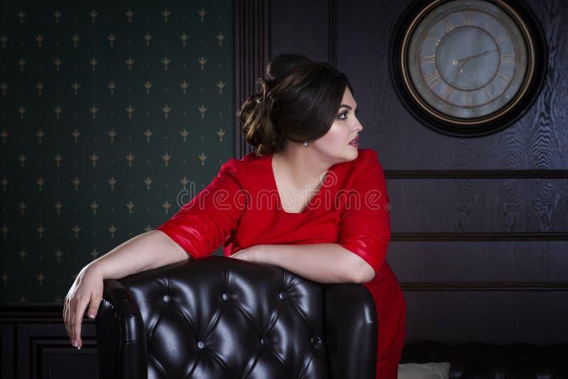 Plus groottemannequin in rode avondjurk, vette vrouw op luxe binnenlands, te zwaar vrouwelijk lichaam royalty-vrije stock foto's