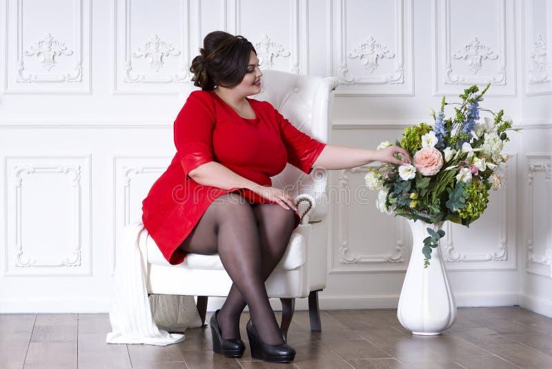 Plus groottemannequin in rode avondjurk, vette vrouw op luxebinnenland stock afbeeldingen