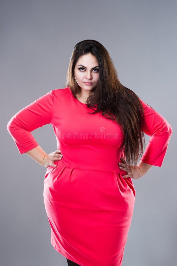 Plus groottemannequin in rode kleding, vette vrouw op grijze achtergrond, lichaams positief concept stock afbeeldingen