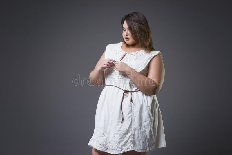 Plus groottemannequin in vrijetijdskleding, vette vrouw op grijze achtergrond, te zwaar vrouwelijk lichaam stock foto