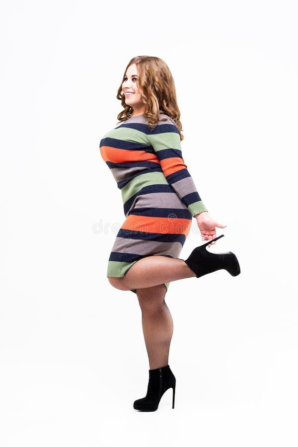 Plus groottemodel in gekleurde gestreepte kleding, sexy vette vrouw op witte achtergrond, lichaams positief concept stock foto