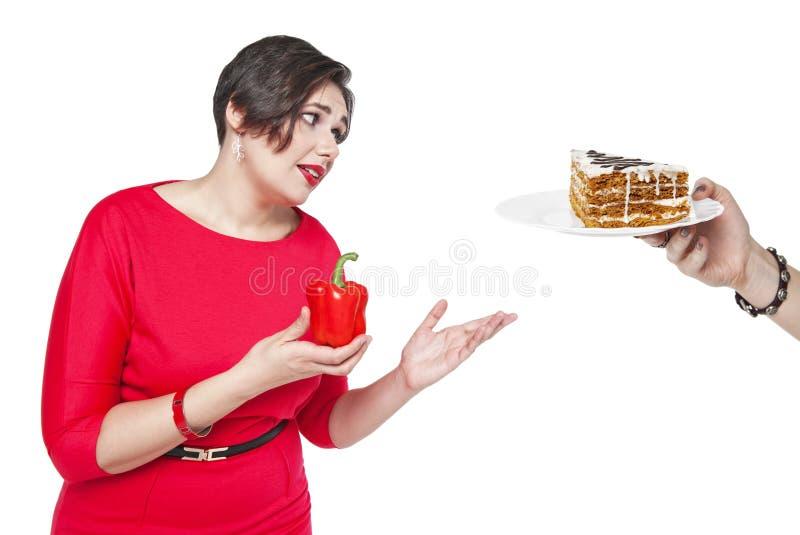 Plus groottevrouw die keus tussen gezond en ongezond voedsel maken stock fotografie