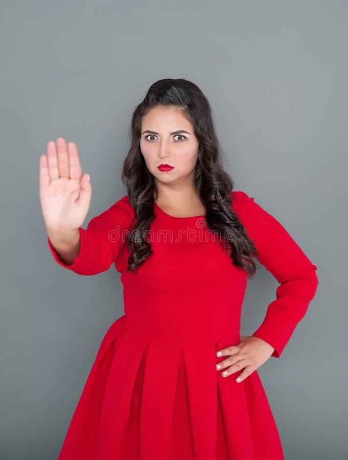 Plus groottevrouw in rode kleding die eindegebaar op grijs tonen royalty-vrije stock afbeeldingen