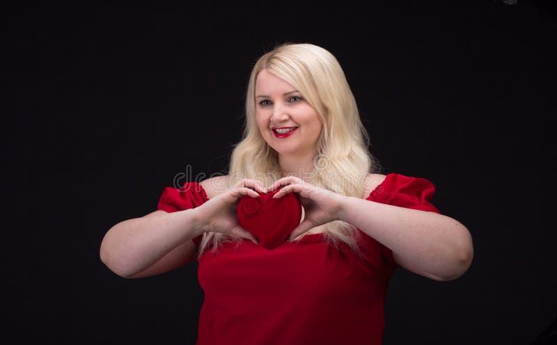 Plus groottevrouw in rode kleding met giftdoos stock afbeelding