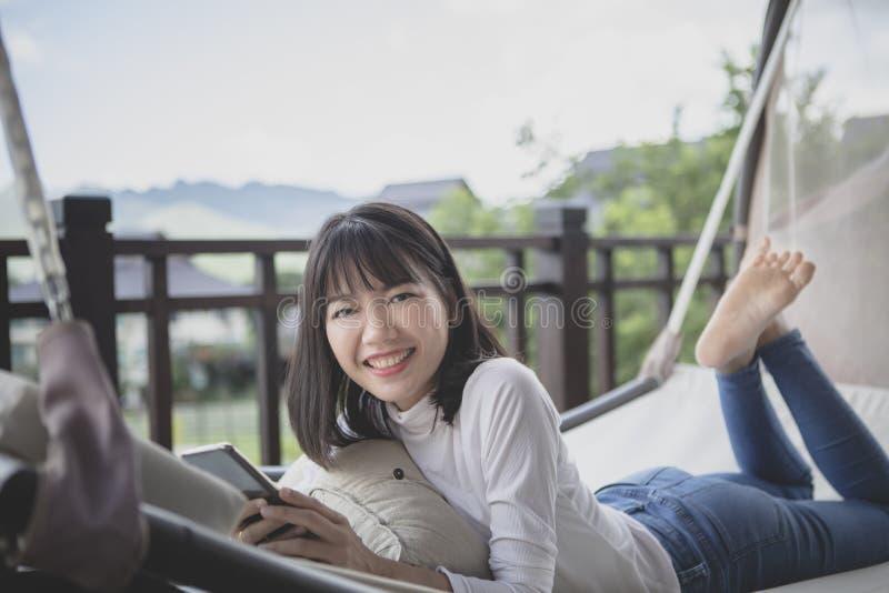 Plus jeune femme asiatique détendant avec le visage de sourire toothy sur un cradl photos stock
