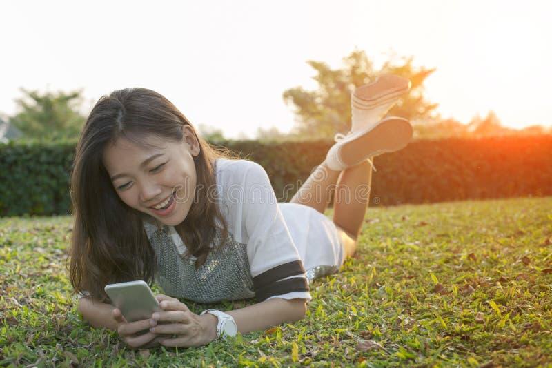 Plus jeune femme asiatique se trouvant sur le champ jouant le téléphone et le rire futés photographie stock